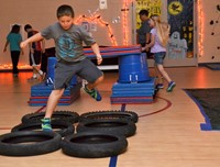 A third grade student runs and jumps through tires in an obstacle course