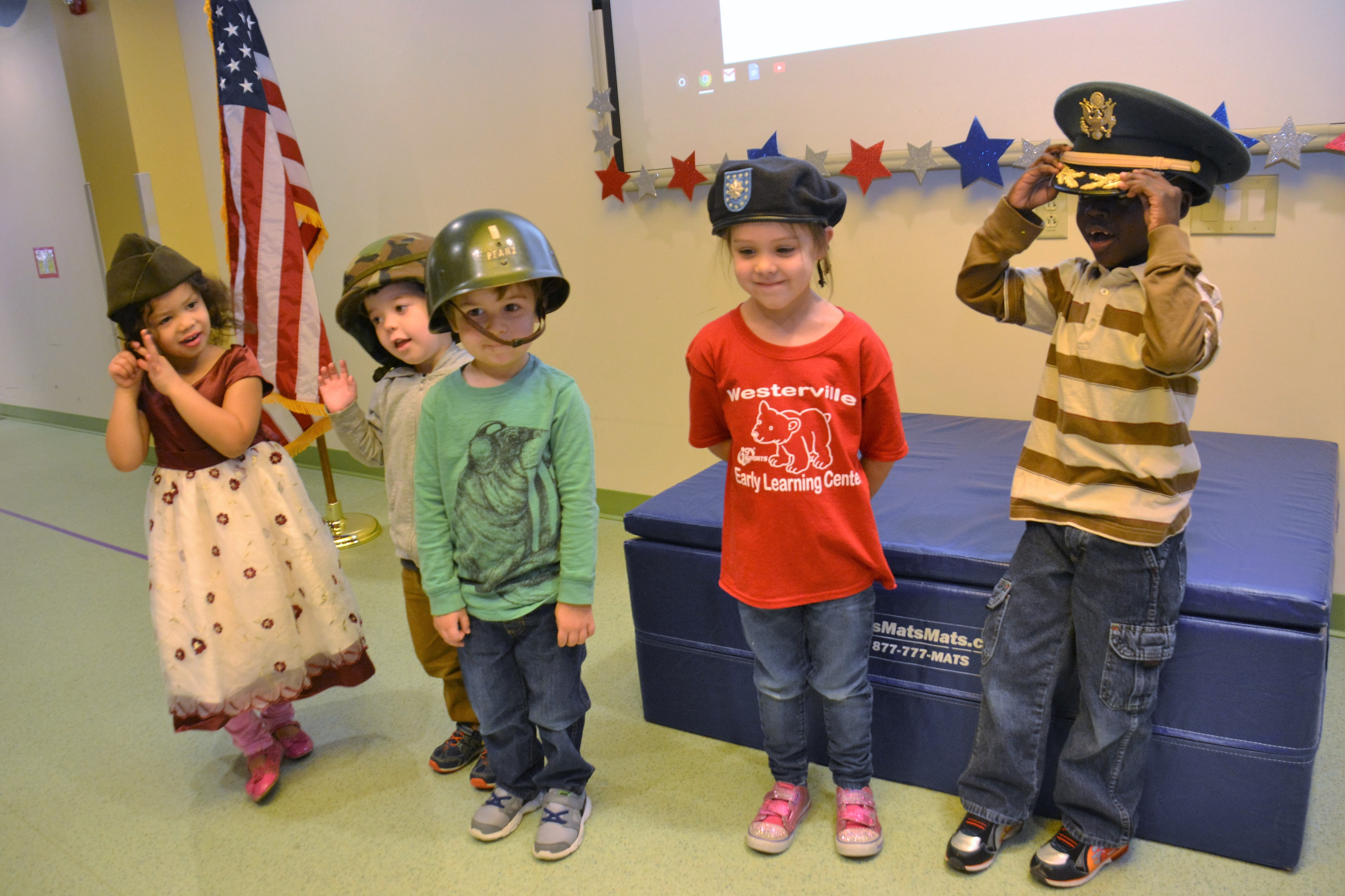 Five pre-school students try on different military headgear.