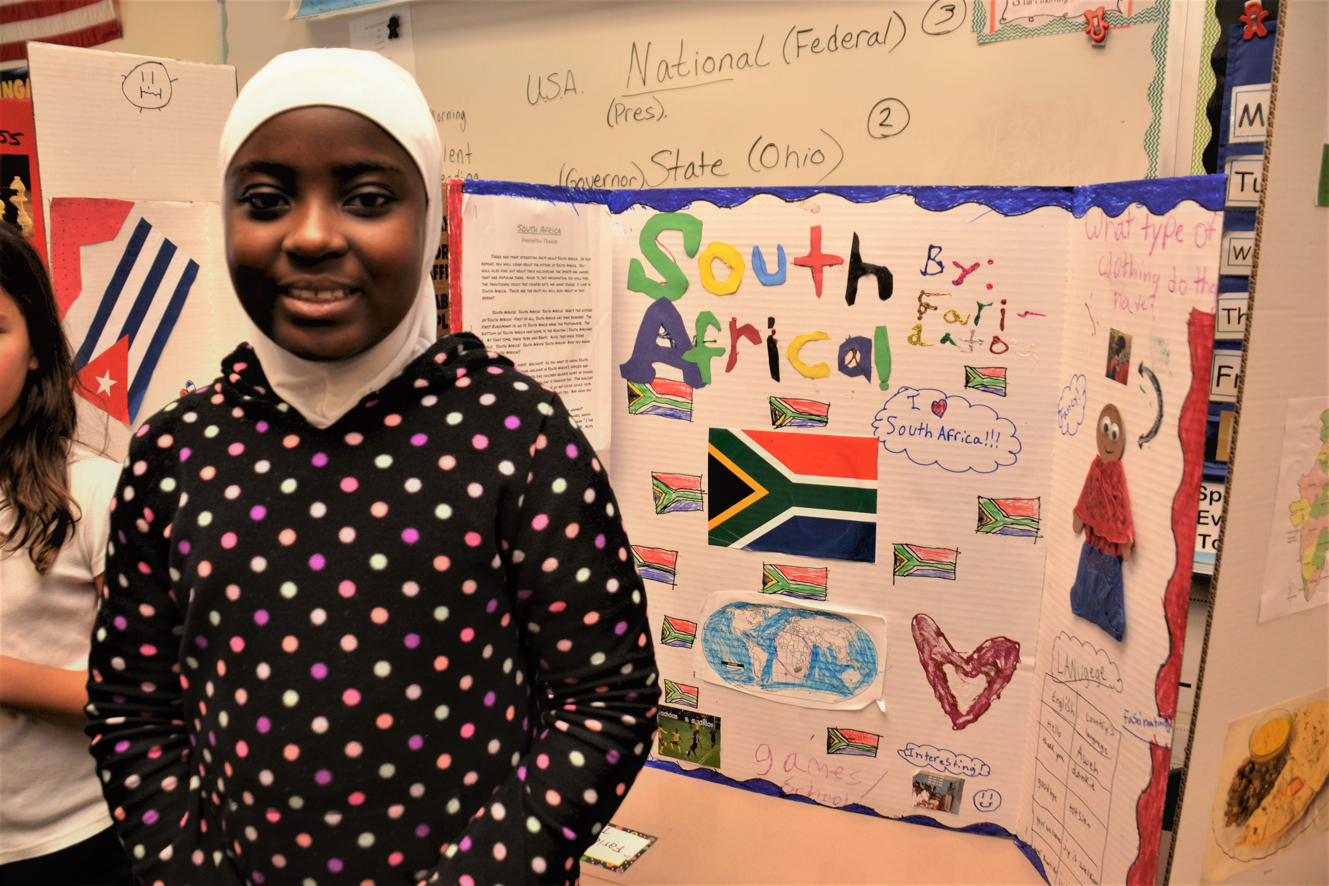 A student stands in front of the South Africa tri-fold board she created