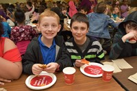 Students enjoy pizza with their classmates.