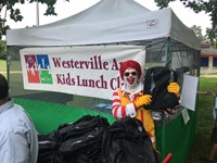Ronald McDonald  at Westerville Area Kids Lunch Club location distributing book bags and school supplies.