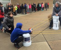 Students use a giant slingshot to launch their protective egg containers